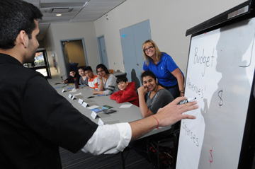 Coast Capital Savings employees explain budgeting concepts to youth attending a public delivery of Dollars with Sense at Guildford Library, Surrey, BC on November 15, 2014.